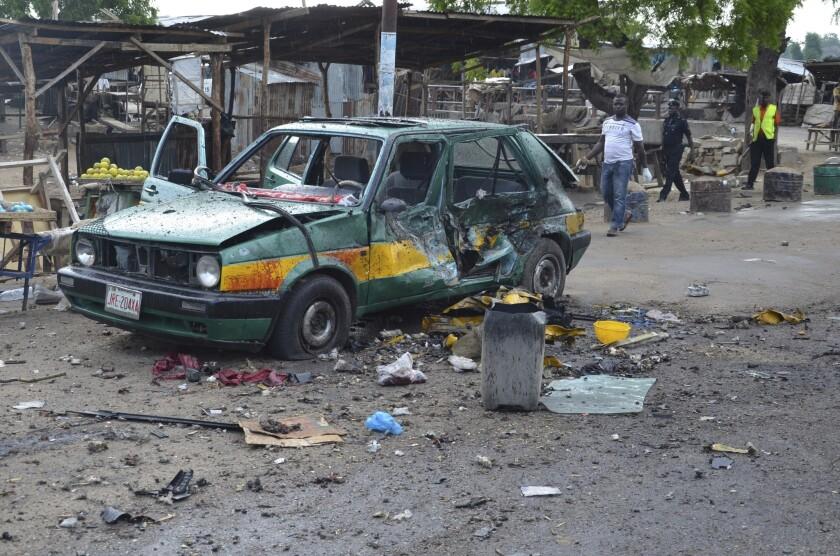 Esta fotografía de archivo muestra gente que pasa cerca de un auto dañado en el sitio donde explotó una bomba, en Maiduguri, Nigeria. Los extremistas del grupo islámico Boko Haram de Nigeria tienen un nuevo líder, según una entrevista publicada el miércoles 3 de agosto de 2016 por el grupo Estado Islámico. (AP Foto/Jossy Ola, archivo)