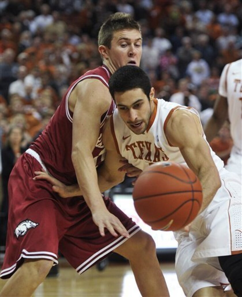 Texas guard Dogus Balbay, front, loses the ball during a drive against Arkansas guard Rotnei Clarke, back, during the first half of an NCAA college basketball game Tuesday, Jan. 4, 2011, in Austin, Texas. (AP Photo/Michael Thomas)