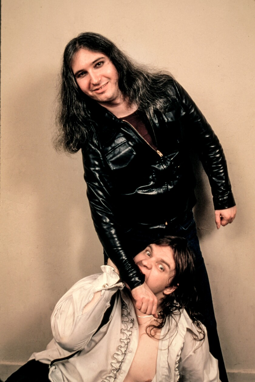 Meat Loaf pretends to bite the arm of Jim Steinman.
