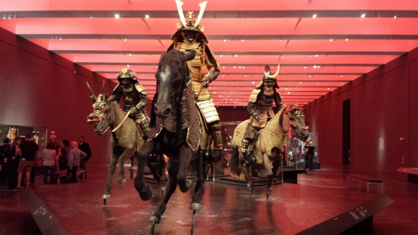 "Warriors galloping on horseback are at the entry to the LACMA exhibition ""Samurai."""