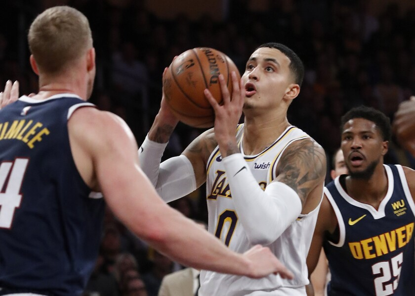 Lakers forward Kyle Kuzma tries to shoot over Denver Nuggets center Mason Plumlee during the second quarter of the Lakers' 128-104 loss Sunday at Staples Center.
