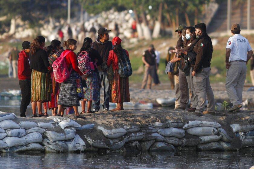 Agentes de inmigración mexicanos revisan las identificaciones de los viajeros guatemaltecos