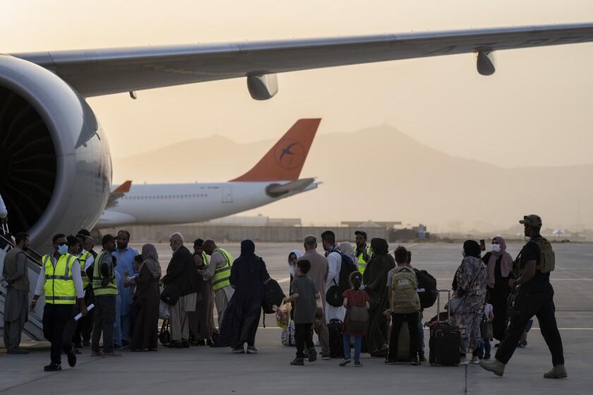 Foreigners board a Qatar Airways aircraft