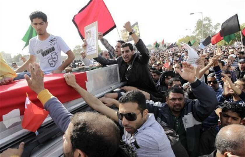 Friends and relatives chant anti-government slogans during the funeral of Mahmoud Maki Abu Taki, 22, who died during clashes between Bahraini anti-government protesters and riot police on Thursday, in Sitra village, Bahrain, Friday, Feb. 18, 2011. (AP Photo/Hassan Ammar)