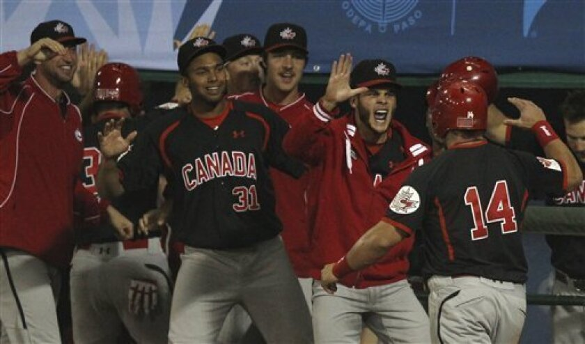 Canada's Tim Smith (14) high fives with teammates after scoring during the sixth inning of the final baseball game against the United States at the Pan American Games in Lagos de Moreno, Mexico, Tuesday Oct. 25, 2011. (AP Photo/Javier Galeano)