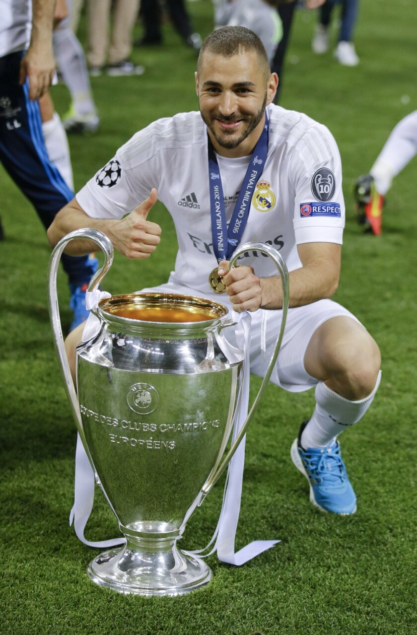 Real Madrid's Karim Benzema poses with the trophy after the Champions League final soccer match between Real Madrid and Atletico Madrid at the San Siro stadium in Milan, Italy, Saturday, May 28, 2016. Real Madrid won 5-4 on penalties after the match ended 1-1 after extra time.  (AP Photo/Andrew Med
