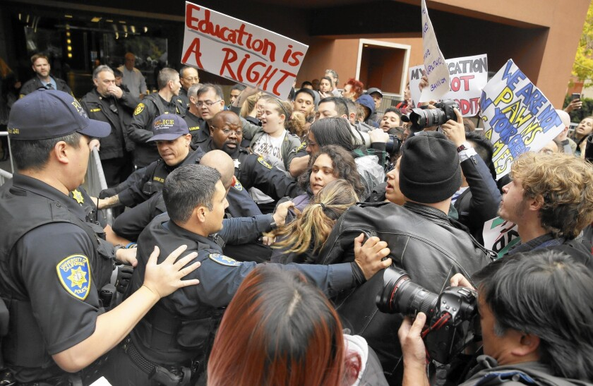 UC campus police push student protesters back behind barricades outside Wednesday's regents committee meeting in San Francisco.