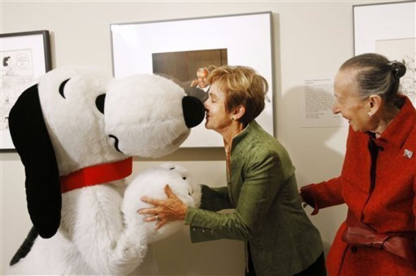 Jean Schulz, center, widow of Charles Schulz, rubs noses with Snoopy, in front of a portrait of Peanuts creator Charles M. Schulz, by photographer Yousuf Karsh, Friday, Oct. 1, 2010, National Portrait Gallery in Washington, during a ceremony where the portrait was presented to the gallery. Estrellita Karsh, wife of the photographer is at right. (AP Photo/Jacquelyn Martin)