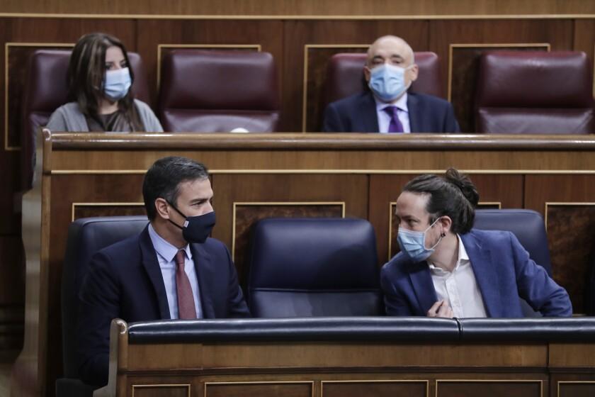 El presidente del gobierno de España, Pedro Sánchez (izquierda), y el vicepresidente segundo, Pablo Iglesias, hablan durante una sesión parlamentaria sobre una moción de censura a Sánchez, en Madrid, el 21 de octubre de 2020. (AP Foto/Manu Fernández, Pool)
