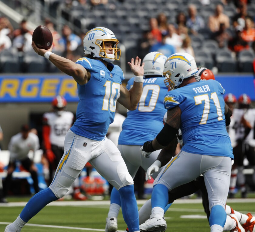 Chargers quarterback Justin Herbert (10) throws as the line pass protects against Brown.