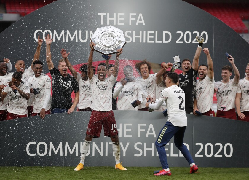 Arsenal's Pierre-Emerick Aubameyang lifts the trophy after winning the English FA Community Shield soccer match between Arsenal and Liverpool at Wembley stadium in London, Saturday, Aug. 29, 2020. (Andrew Couldridge/Pool via AP)