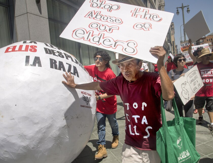 Mario Canel, 73, pushes a papier-mache ball through the streets of downtown L.A. as he protests his eviction