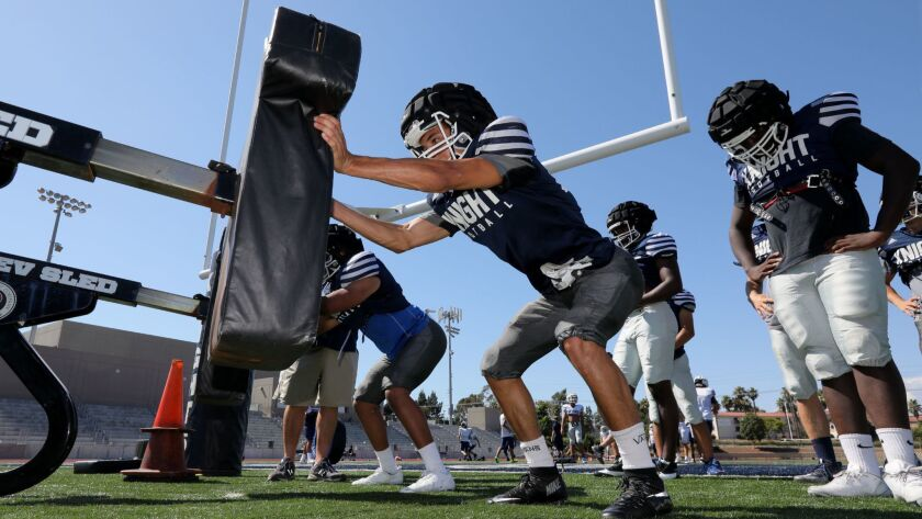 Afternoon football practice at San Marcos High School- Zack Frost, close, takes his turn pushing the sled in the afternoon heat.