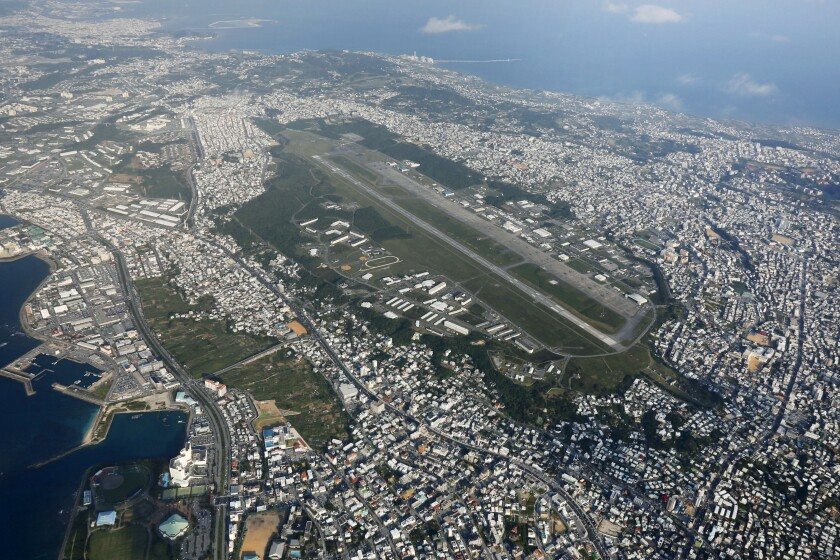 """FILE - This October 2015, aerial file photo shows U.S. Marine Corps Air Station Futenma in Ginowan, Okinawa, southern Japan. Japanese defense minister said on Tuesday, July 14, 2010 that officials have discovered """"a number of problems"""" with the U.S. military's coronavirus measures for its service members stationed in Japan after about 100 Marines have tested positive for the virus in a massive outbreak at multiple bases in Okinawa. Most of cases are at the air station. (Kazuhiko Yamashita/Kyodo News via AP, File)"""