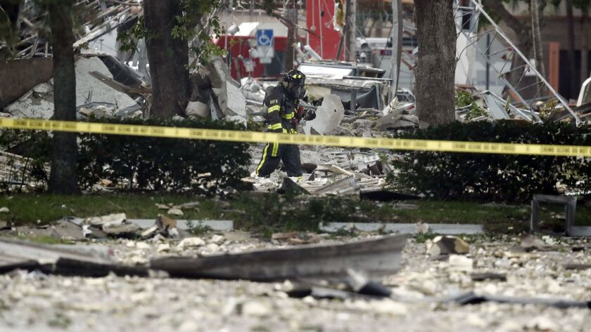 A firefighter walks through the remains of a building after an explosion on Saturday, July 6, 2019,