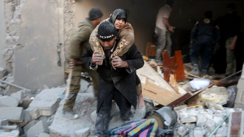 A Syrian rescuer carries a woman from the rubble of a building after reported airstrikes on a rebel-held district in Aleppo on Sunday.