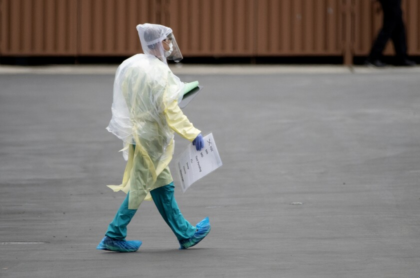 A medical professional carries a car tag used to identify symptoms at a drive-through coronavirus testing place in March.