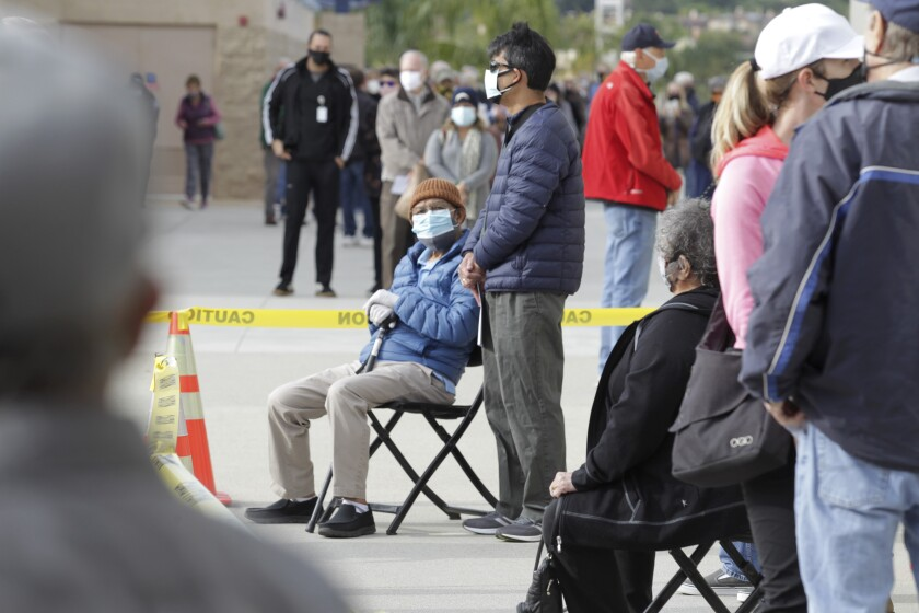 Rick Baylon, 87, takes a seat as he waits in line with his son at a new vaccination super station at CSU San Marcos Sunday.