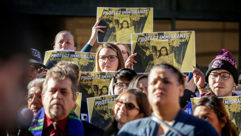 Immigrants' rights advocates and members of the immigrant community rally before a Los Angeles County Board of Supervisors meeting in December.