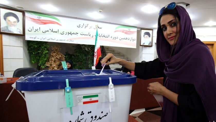 An Iranian woman, residing in Kuwait, casts her ballot for presidential and municipal elections on M