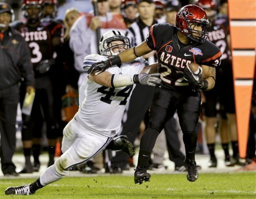 San Diego State running back Chase Price breaks a tackle by BYU's Brandon Ogletree after catching a pass during the first half of the Poinsettia Bowl NCAA college football game, Thursday, Dec. 20, 2012, in San Diego. (AP Photo/Lenny Ignelzi)