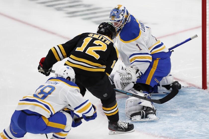 Boston Bruins' Craig Smith (12) scores on Buffalo Sabres' Ukko-Pekka Luukkonen (1) during the first period of an NHL hockey game, Saturday, May 1, 2021, in Boston. (AP Photo/Michael Dwyer)