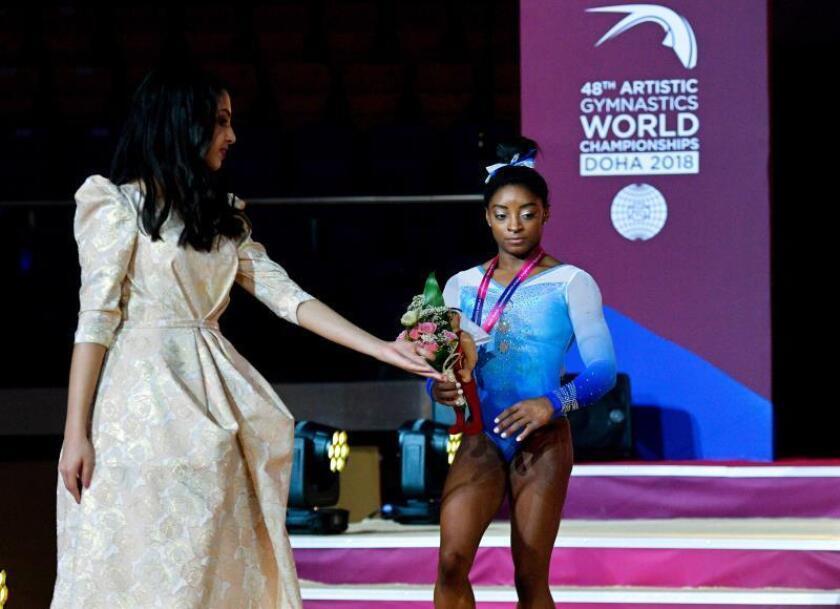 La gimnasta estadounidense Simone Biles (dcha) celebra en el podio la medalla de plata conseguida en la prueba de barras asimétricas del Mundial de Gimnasia Artística que se disputa en Doha, Catar, el 2 de noviembre de 2018. EFE