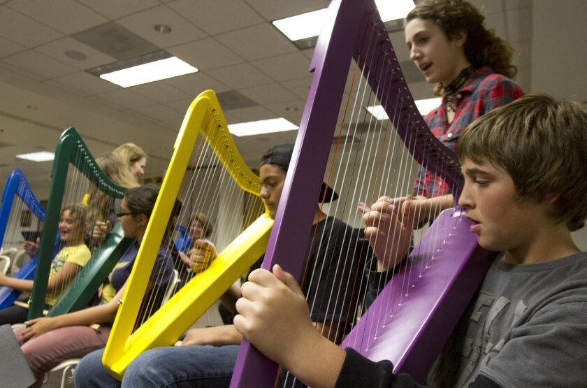 Joey Sorenesn, 11, right, and other students during harp class Monday at the Museum of Making Music in Carlsbad.