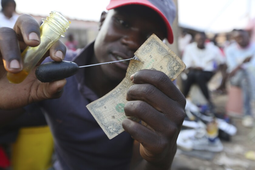 A currency trader mends a worn $2 bill at a market in Harare, the capital of Zimbabwe.