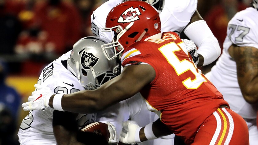 Chiefs linebacker Justin Houston (50) brings down Raiders running back Latavius Murray during the first half of their game Dec. 8.