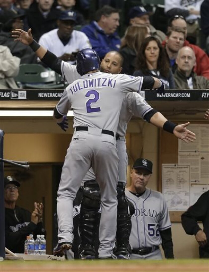 Colorado Rockies' Troy Tulowitzki (2) gets a hug from Yorvit Torrealba after Tulowitzki's home run against the Milwaukee Brewers during the third inning of a baseball game Tuesday, April 2, 2013, in Milwaukee. (AP Photo/Jeffrey Phelps)