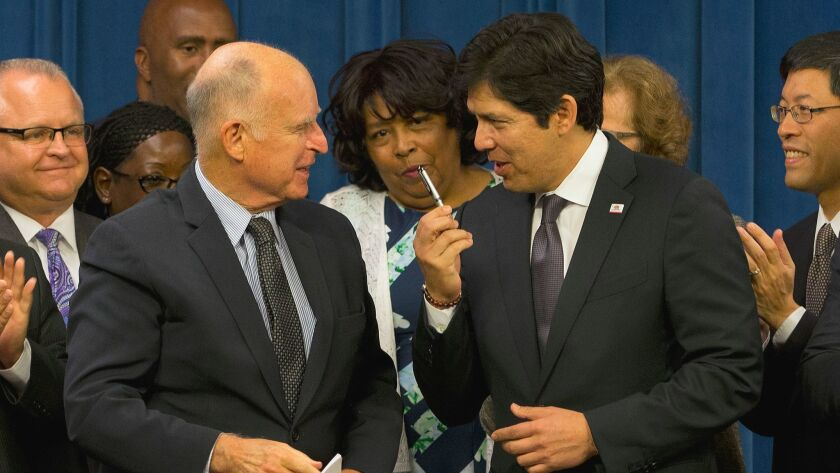 California Senate President Pro Tem Kevin de León (D-Los Angeles), right, thanks Gov. Jerry Brown after he signed legislation that will automatically enroll millions of private-sector workers in retirement saving accounts at the Capitol on Sept. 29, 2016, in Sacramento, Calif.