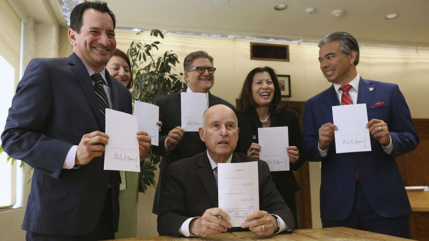 Gov. Jerry Brown holds a copy of a bill to end bail he signed Tuesday. The bill, co-authored by state Sen. Bob Hertzberg, D-Van Nuys, third from right, and Assemblyman Rob Bonta, D-Alameda, right, makes California the first state to eliminate bail for suspects awaiting trial.