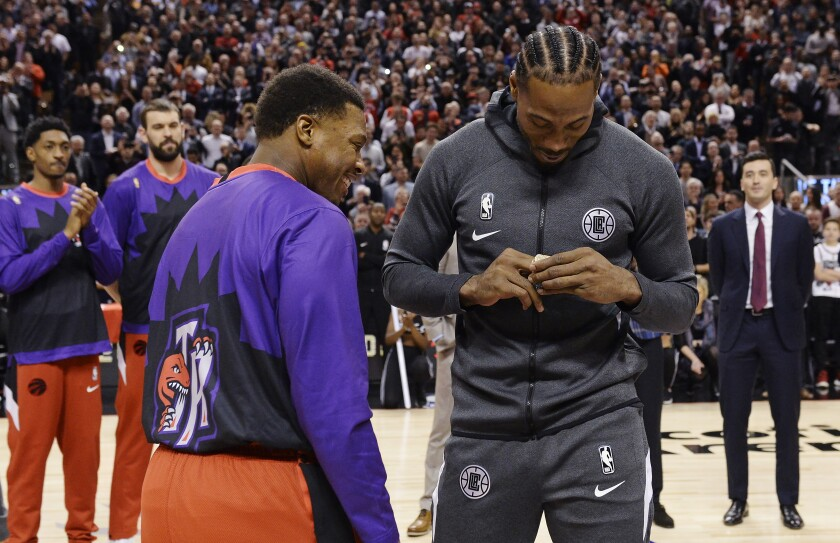 Clippers forward Kawhi Leonard is present with high 2019 NBA championship ring by former teammate Kyle Lowry before the game against the Raptors on Dec. 11, 2019, in Toronto.