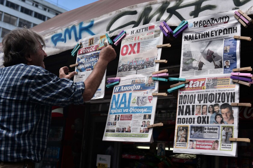 """A news agent hangs newpapers bearing """"no"""" and """"yes"""" headlines in central Athens on the eve of the Greek referendum on bailout terms."""
