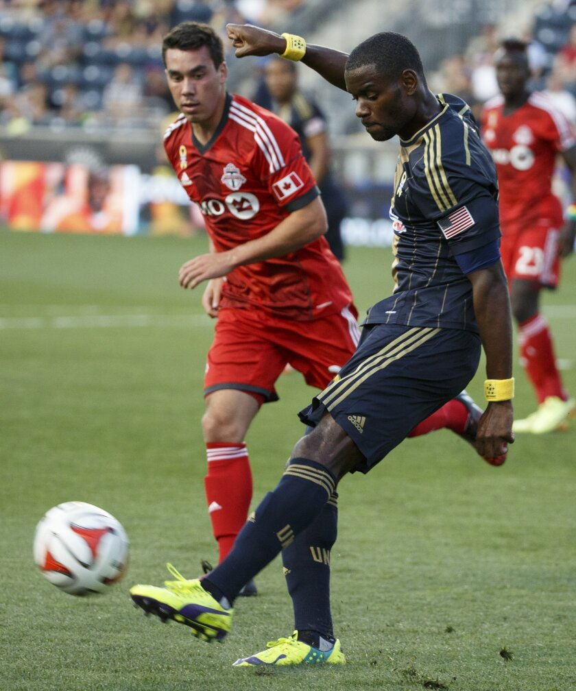 Philadelphia Union's Maurice Edu, right, kicks the ball up the field past Toronto FC's Daniel Lovitz, left, during the first half of an MLS soccer match, Wednesday, Sept. 3, 2014, in Chester, Pa. (AP Photo/Chris Szagola)