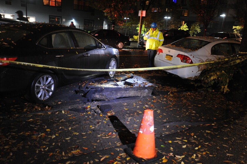 A Con Edison emergency technician inspects an exploded manhole on E. 156th St. in Melrose, the Bronx. Three civilians and two police officers were reported hurt.