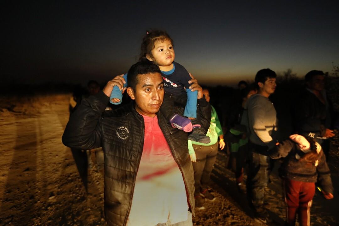 An asylum seeker carries a child