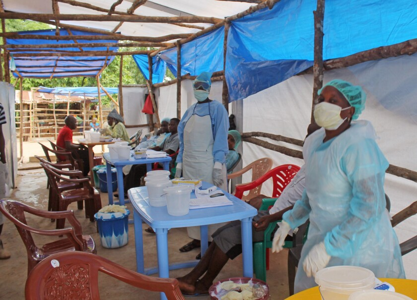 Medical personnel work at a clinic where Ebola patients are cared for on the outskirts of Kenema, Sierra Leone. A leading Sierra Leone doctor died of the disease July 29.