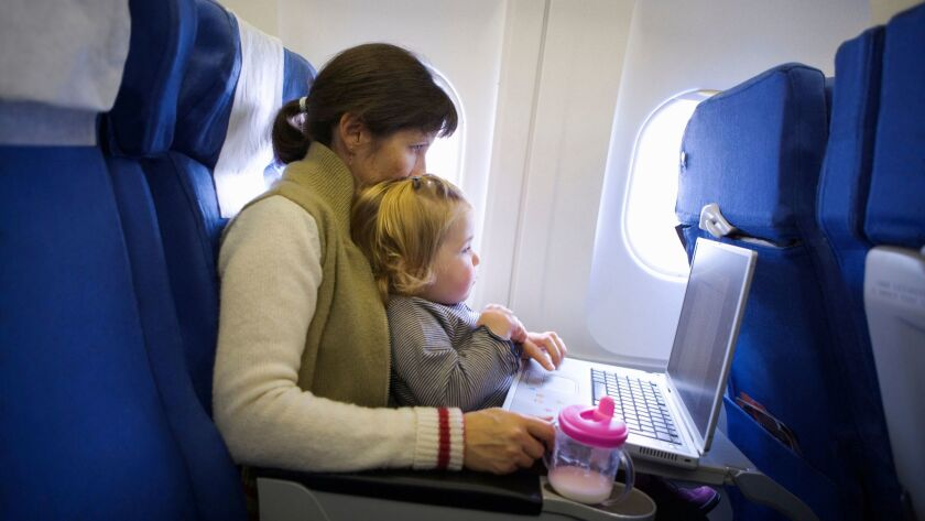Woman using laptop with daughter (2-4) on lap, on airplane ** OUTS - ELSENT, FPG, CM - OUTS * NM, PH
