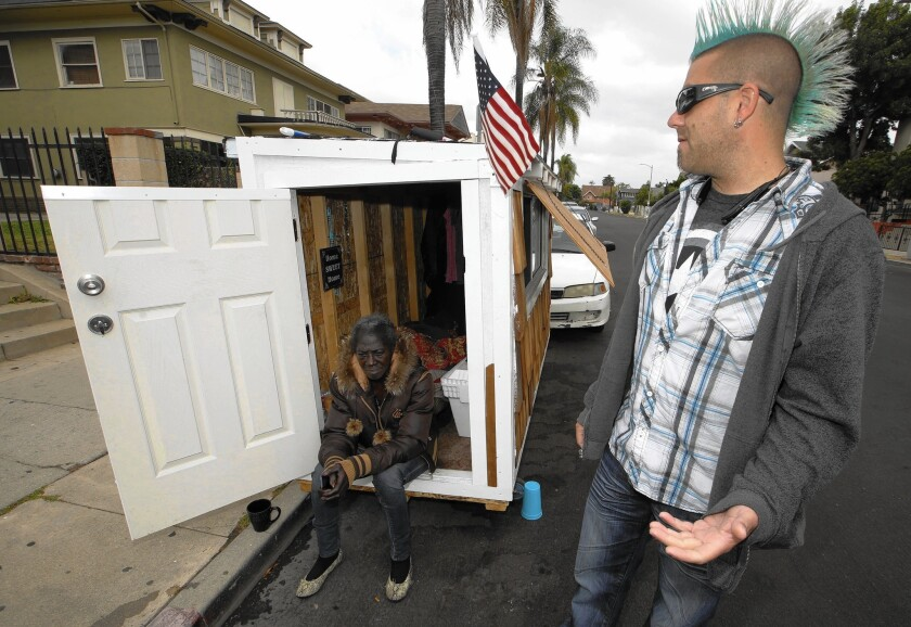 """Los Angeles resident Elvis Summers, right, poses with the tiny house on wheels that he built for Irene """"Smokie"""" McGhee, 60, a woman who had been sleeping on the streets in his South Los Angeles neighborhood, on May 7, 2015."""