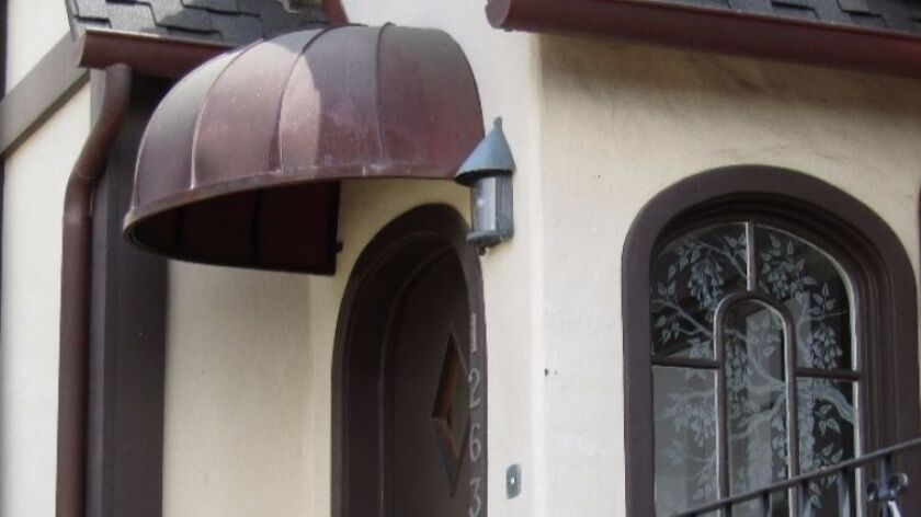 The copper awning detail framing the front door was added by Helen Copley after she purchased the pr