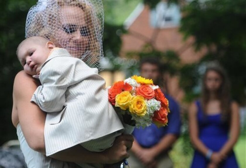 FILE - This Aug. 3, 2013 file photo, Christine Swidorsky carries her son and the couple's best man, Logan Stevenson, 2, down the aisle to her husband-to-be Sean Stevenson during the wedding ceremony in Jeannette, Pa. Christine Swidorsky Stevenson says on her Facebook page that Logan died in her arms at 8:18 p.m. Monday, Aug. 5, 2013, at their home in Jeannette, about 25 miles east of Pittsburgh.