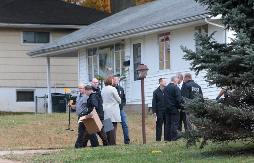 In a Wednesday, Oct. 28, 2015 photo, police officers investigate at the scene of a shooting on Paddington Drive in Normandy, Mo. Authorities say a St. Louis-area officer who exchanged gunfire with an 18-year-old suspect never hit him, even as the suspect's father questioned police claims that the s
