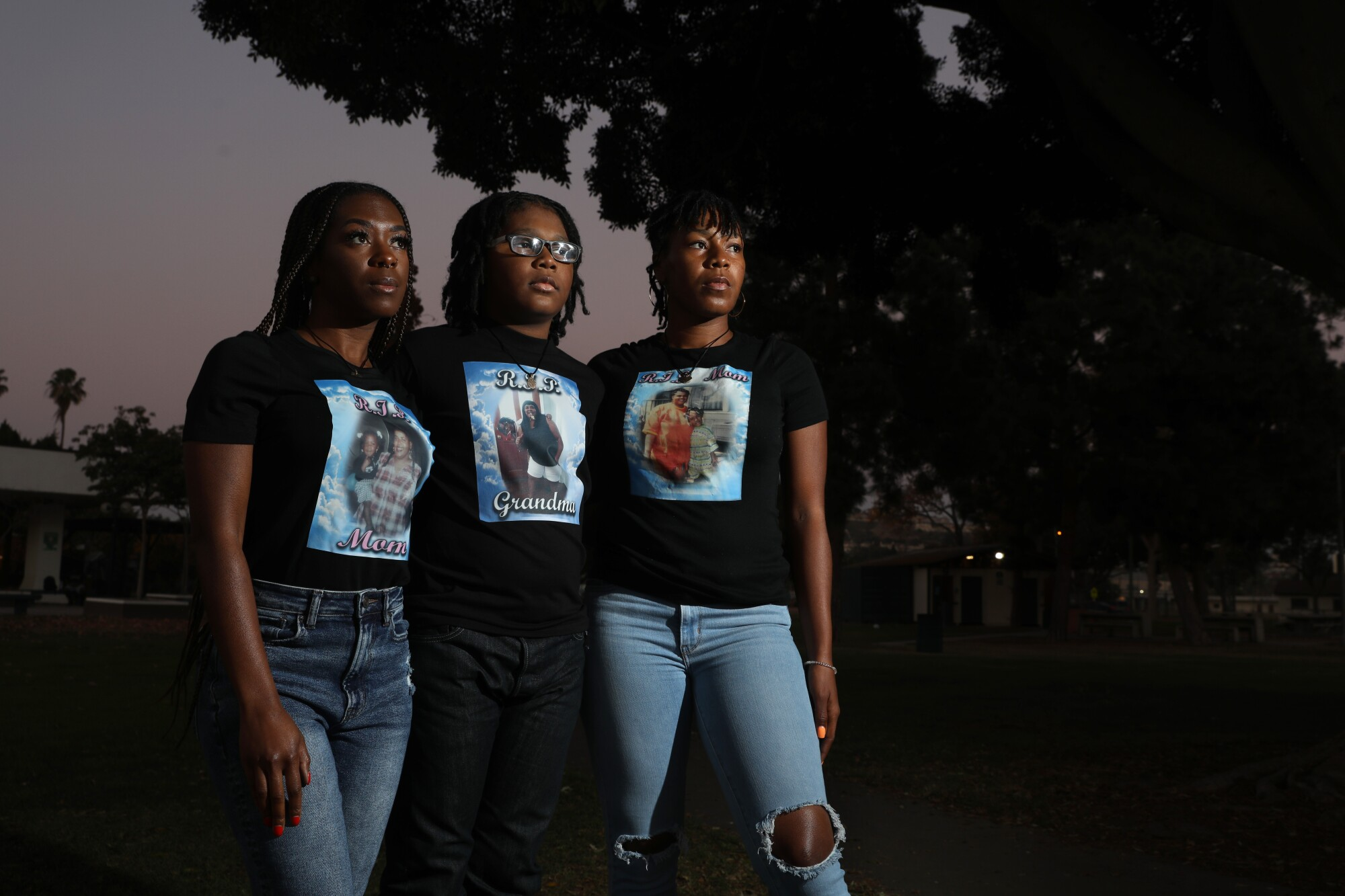 Two women and a boy stand for a portrait wearing T-shirts with images of a slain woman.