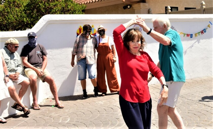 Nancy Scott dances with husband, Mike, at a mariachi surprise birthday party on July 18 outside her La Jolla home.