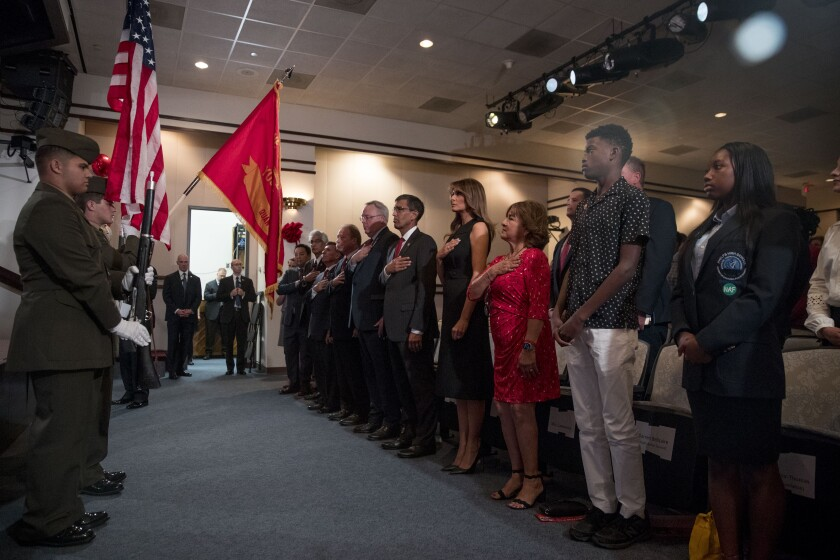First lady Melania Trump, center, and acting DEA Administrator Uttam Dhillon, center left, stands at a Red Ribbon Rally at the Drug Enforcement Agency in Arlington, Va., Monday, Oct. 7, 2019. Also pictured is Mika Camarena, third from right, the wife of former DEA agent Kiki Camarena who was killed in 1985 while on assignment in Mexico. (AP Photo/Andrew Harnik)
