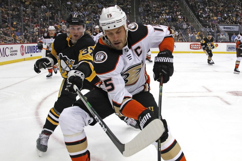 Ducks' Ryan Getzlaf (15) goes after the puck in the corner with Pittsburgh Penguins' Sam Lafferty (37) during the second period on Thursday in Pittsburgh.