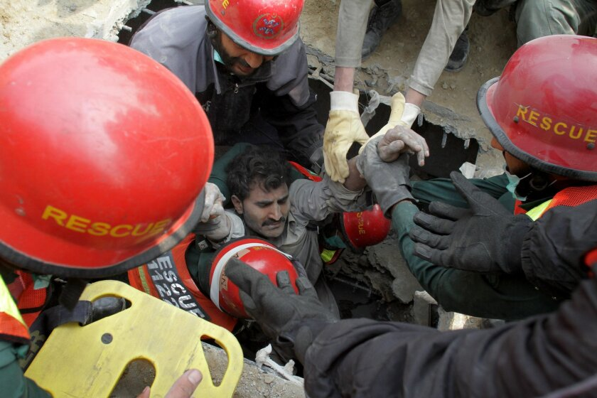 Pakistani volunteers rescue a man trapped in Lahore, Pakistan, Thursday, Nov. 5, 2015. A factory building under construction in an industrial area on the outskirts of Pakistan's eastern city of Lahore collapsed, killing many workers and injuring dozens, officials said. (AP Photo/K.M. Chaudary)