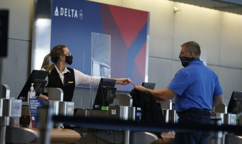 Delta Air Lines worker hands a boarding pass to a passenger